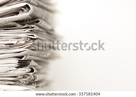 A stack of newspapers. Focus on near edge of stack.
