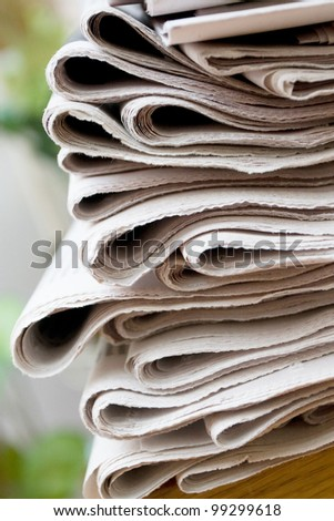 A stack of newspapers with focus on front - stock photo