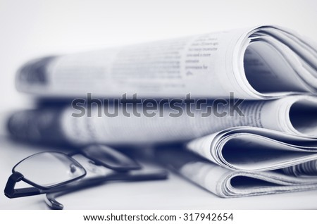 A stack of newspapers with glasses. Shallow depth of field. - stock photo