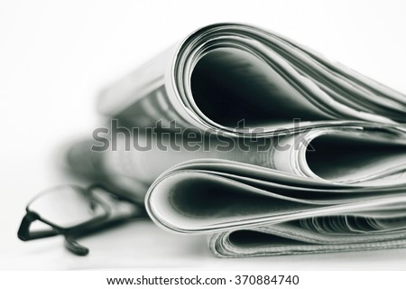 A stack of newspapers with glasses. Shallow depth of field.
