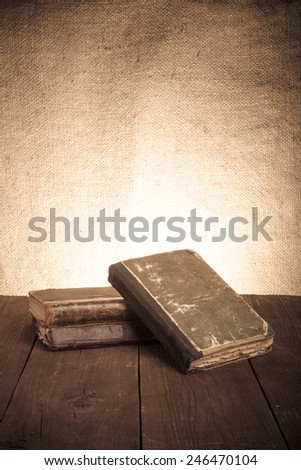 A stack of old books on old wooden table against the background of burlap. Toned - stock photo