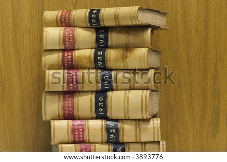 A stack of old law reports against a wood background - stock photo