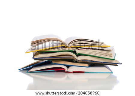A stack of opened textbooks on a white background - stock photo