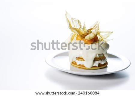 a stack of pancakes with cream and decorated with physalis on white background