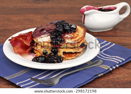 A stack of pancakes with fresh, homemade blueberry sauce with a side of bacon.  Selective focus on front of stack.