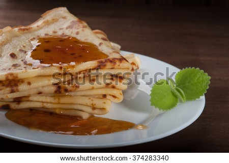 A stack of pancakes with jam on a white plate on dark wooden background