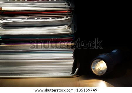 A stack of papers and a flashlight on a desk in a low light scene