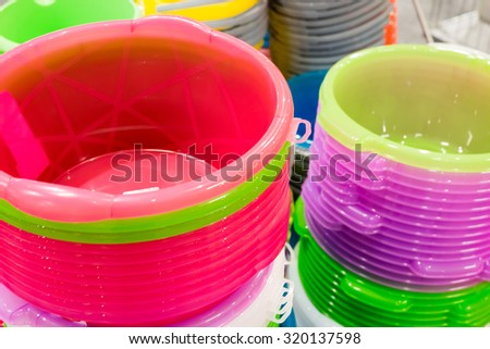 A stack of plastic bucket of different colors