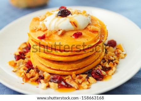 A stack of pumpkin pancakes with walnuts, cranberries, honey and yogurt - stock photo