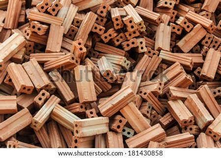 A stack of red clay bricks on construction site background - stock photo
