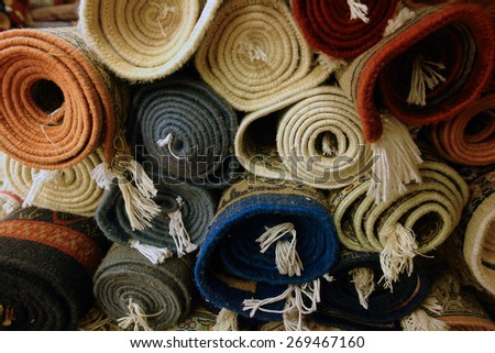 A stack of rolled-up mats or carpets in a variety of colors viewed end-on, in a carpet store in India. - stock photo