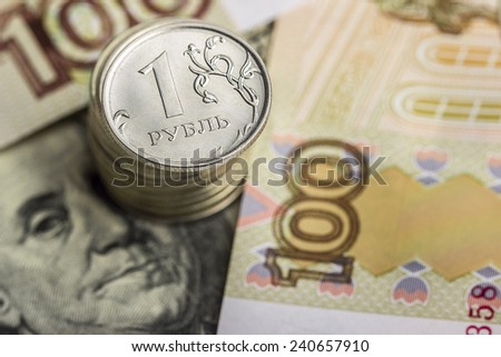 A stack of Russian coins on money background: Russian rubles and US dollars - stock photo