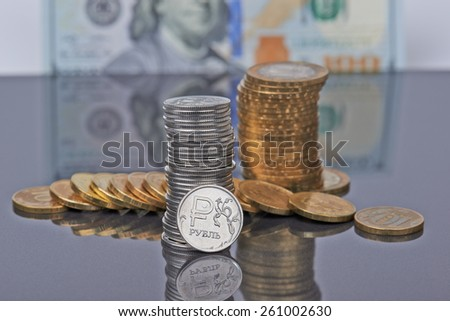 A stack of Russian coins on the background of US dollar - stock photo
