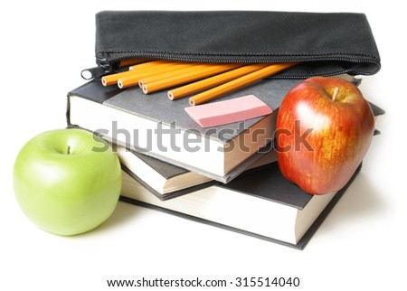 A stack of school books with an open pencil case and some apples. - stock photo