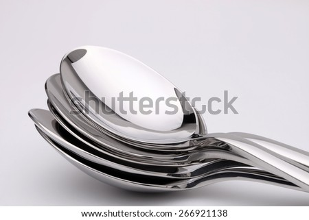 A stack of stainless steel spoons, photographed over a plain background