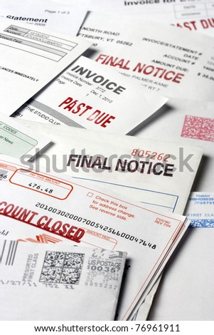 A stack of statements and invoices indicating a past due status on the accounts. Vertical shot.
