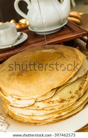 A stack of thin pancakes with honey and butter