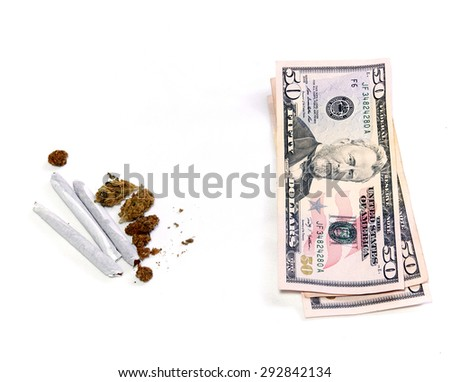 A stack of three 50 dollar US bills is shown beside a cluster of marijuana pot buds and three joints, over white. - stock photo