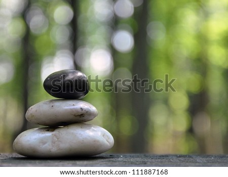 A stack of three zen rocks are in the forest with trees in the background to add a text message. - stock photo