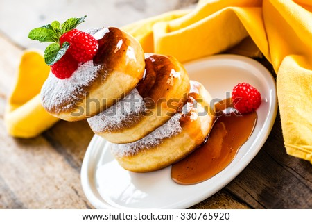 A stack of tree delicious german doughnuts powdered with sugar decorated with raspberry and raspberry sauce on white plate and yellow napkin - stock photo
