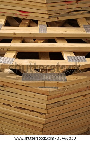 A stack of wooden roof trusses to frame a new house being built, as delivered to the construction site. - stock photo