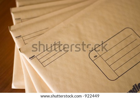 A stack of yellow padded envelopes - stock photo