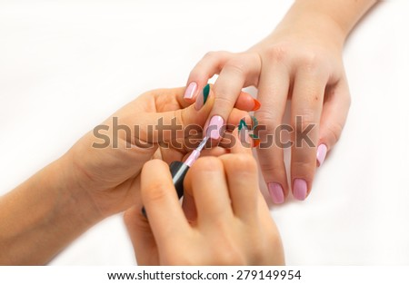 a stage of manicure process: nail polish application isolated on white closeup