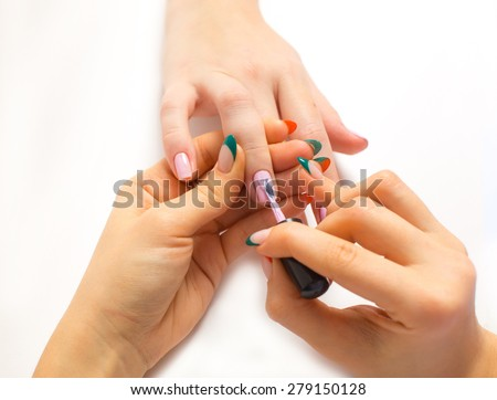 a stage of manicure process: nail polish application isolated on white closeup - stock photo