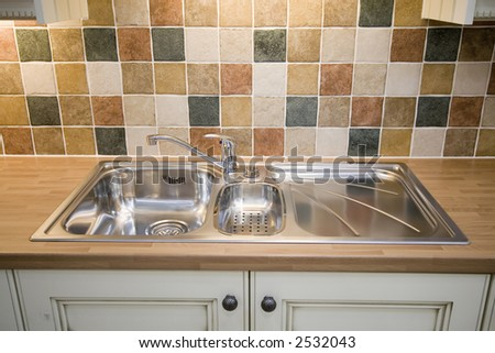 A stainless steel kitchen sink - stock photo