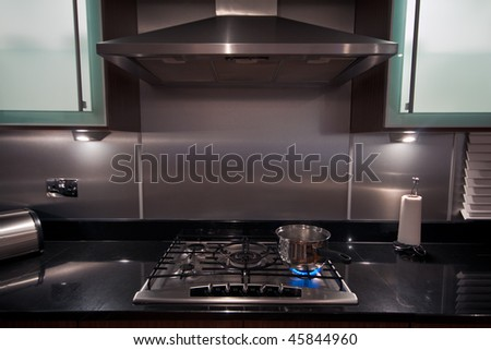 A stainless steel pan on a gas hob in a modern kitchen. - stock photo