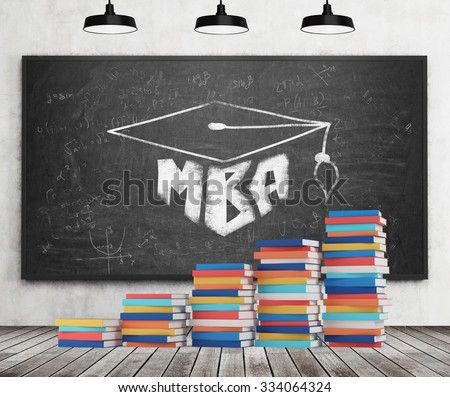 A stair is made of colourful books. A graduation hat is drawn on the black chalkboard. MBA concept. Concrete wall, wooden floor and three black ceiling lights. - stock photo