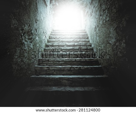A stairway leading to a light.  - stock photo