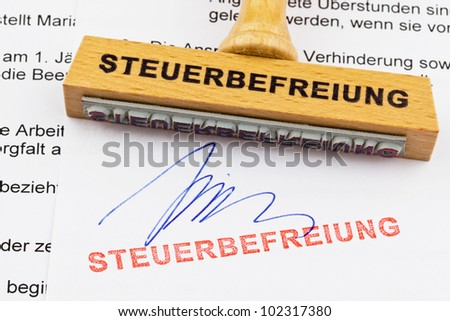 a stamp made of wood lying on a document. german words: exemption - stock photo