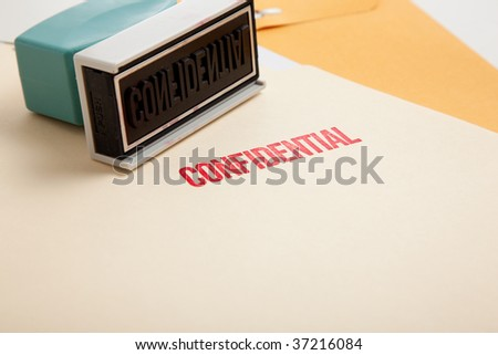 "A stamp with the word ""confidential"" on a stack of folders with copy space"