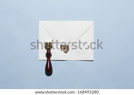 a stamped enveloped on a pale blue background - stock photo