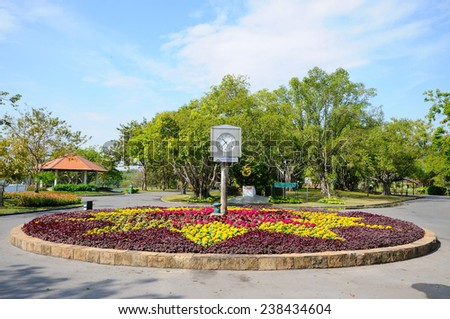 A Stand Clock at the Center of Beautifully Grown Flowers in a Park - stock photo
