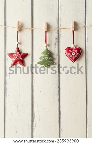 A star, a tree and a heart hanging on a clothesline on a white wooden background. - stock photo