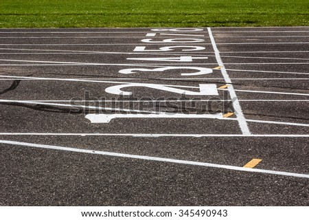 A starting line, with the white lanes numbers and lines, on a black asphalt running track.