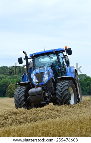A stationary blue tractor is parked on the edge of a field of barley against an overcast sky. - stock photo