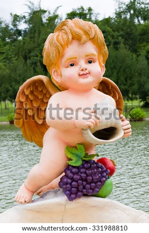 A statue of a baby angel in a public park. - stock photo