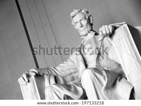 A statue of a man sitting in a chair. - stock photo