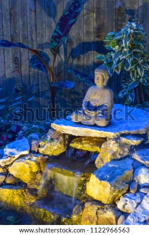 Statue buddha overlooks backyard doityourself japanese stock photo a statue of buddha overlooks a backyard do it yourself japanese zen garden with solutioingenieria Image collections