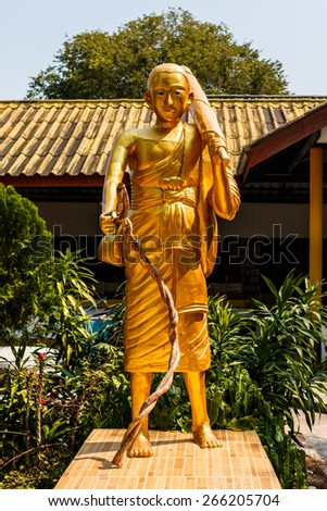 A statue of hiking monk carrying an umbrella in a Buddhist temple. - stock photo