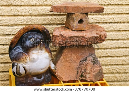 A statue of Japanese raccoon dog (called Tanuki in Japan), in front of the building for the charm and luck, in Takayama, Japan - stock photo