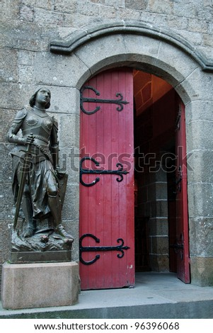A statue of Joan of Arc stands outside a red door at the Church of St. Pierre, Mont St. Michel, France - stock photo