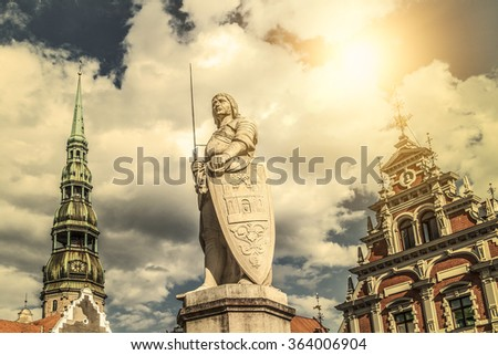 A statue of Riga patron saint - St Roland, stands between the House of Blackheads and the Town Hall. - stock photo