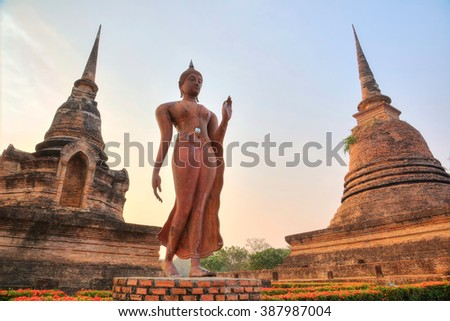 A statue of walking Buddha between Stupas in Wat Sa Si Temple at dusk in Sukhothai Historical Park ~ Beautiful sculpture & ancient architecture in a Buddhist temple of UNESCO Heritage Site in Thailand - stock photo