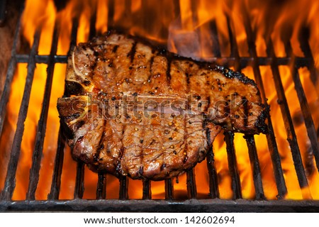 A steak flame broiled on a barbecue, shallow depth of field. - stock photo