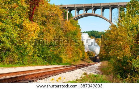 A steam locomotive rounds a curve in the distance under a high arched bridge south of Cleveland, Ohio