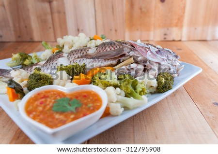 A Steamed Tilapia fish garnish with vegetables.Selective focus. Very shallow Depth of Field, for soft background.